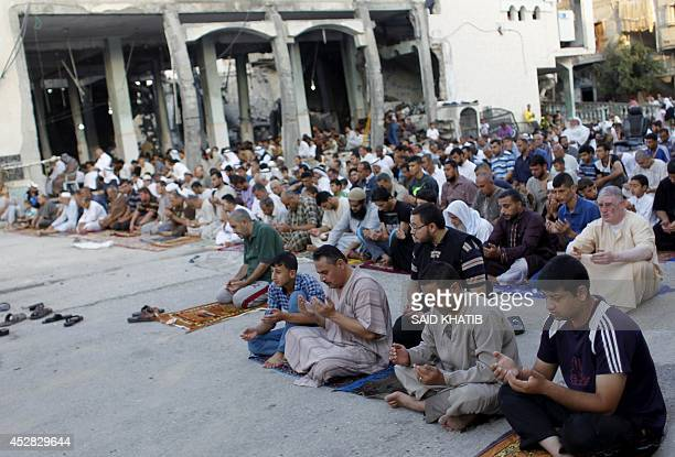 Palestinian Muslims perform a prayer on July 28 on the first day of Eid alFitr outisde the heavily damaged AlFaruq mosque destroyed a week ago by an...
