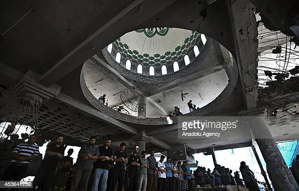 Palestinian Muslims perform Friday Prayer at some parts remaining standing after Israeli attacks of AlSusi Mosque in Gaza City Gaza on August 15 2014...