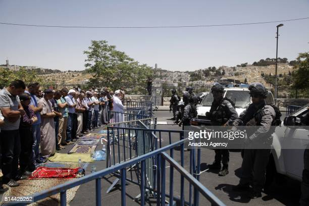 Palestinian Muslims perform Friday prayer near the Lion's Gate and Damascus Gate after AlAqsa Mosque's doors was closed for Friday prayers by Israeli...