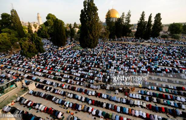 Palestinian Muslims perform the morning Eid alFitr prayer at the AlAqsa Mosque compound Islam's third most holy site in the Old City of Jerusalem on...