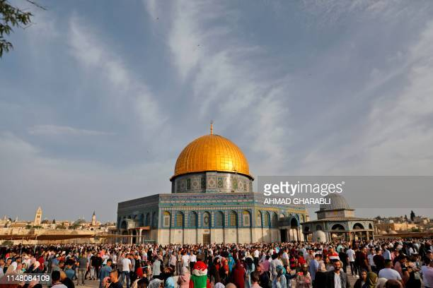 Palestinian Muslims perform the morning Eid alFitr prayer near the Dome of Rock mosque at the AlAqsa Mosque compound Islam's third most holy site in...