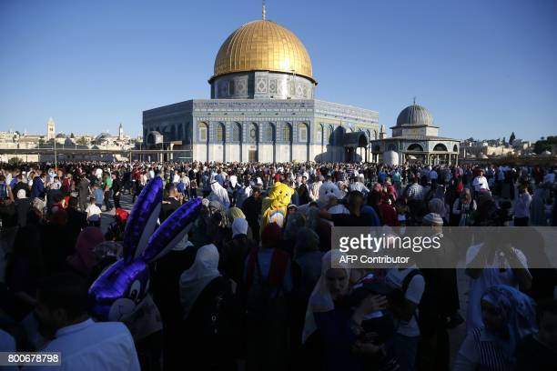 Palestinian Muslims perform the morning Eid alFitr prayer near the Dome of Rock at the AlAqsa Mosque compound Islam's third most holy site in the Old...
