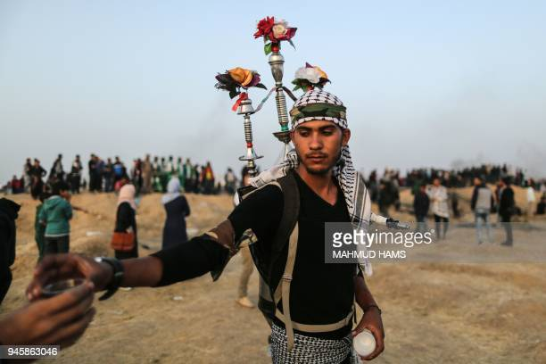 Palestinian national Mohammed safy aged 22 distributes liquorice juice to protesters during a demonstration near the Israeli border fence east of...