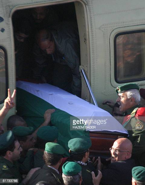 Palestinian negotiations minister Saeb Erakat helps to unload the coffin of late Palestinian leader Yasser Arafat from the helicopter that landed...