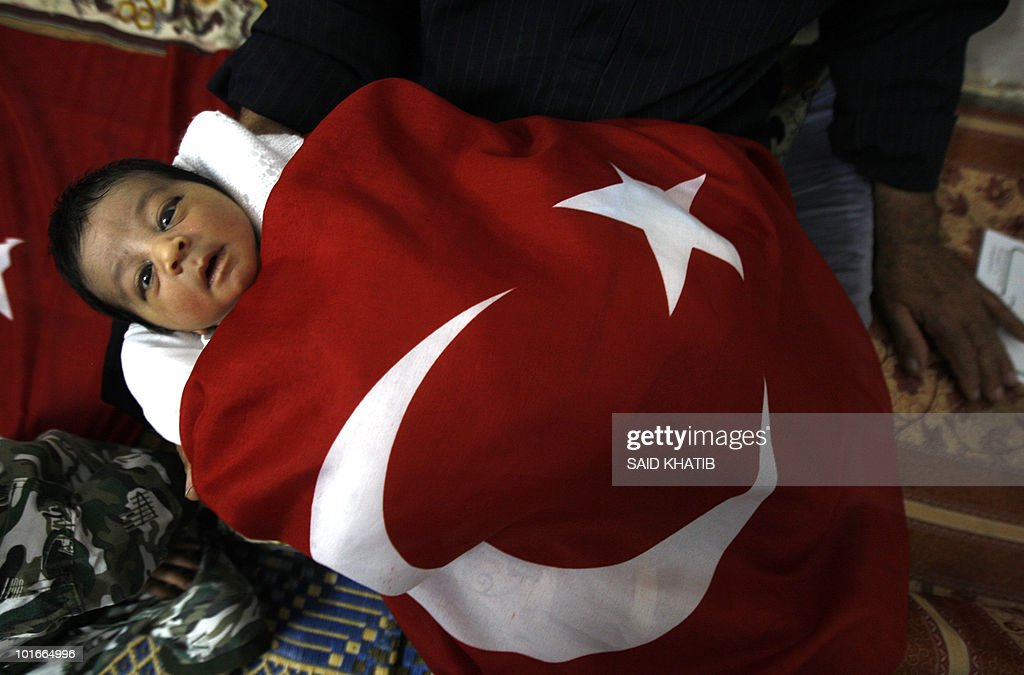 Palestinian newborn Rajab Erdogan, is held by his father (unseen) wrapped in a Turkish flag for members of the media, at their home in the southern Gaza Strip refugee camp of Khan Yunis, June 6, 2010, one day after the baby was born and a week after Turkish humanitarian activists were killed by Israeli comamnados on a flotilla of ships carrying humanitarian aid to the Gaza Strip. Turkey's current Prime Minister is Recep Tayyip Erdogan