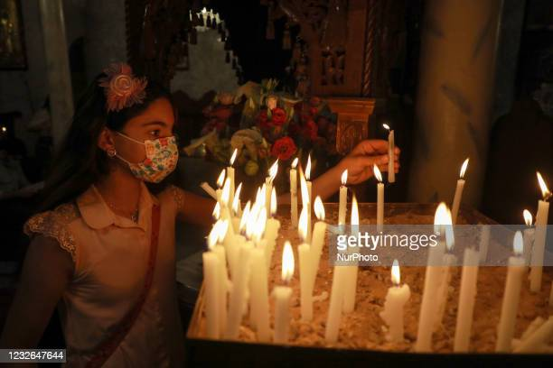 Palestinian Orthodox Christian girl holds a candle during Easter Vigil mass in Gaza City on May 2, 2021. Christians around the world mark the Holy...