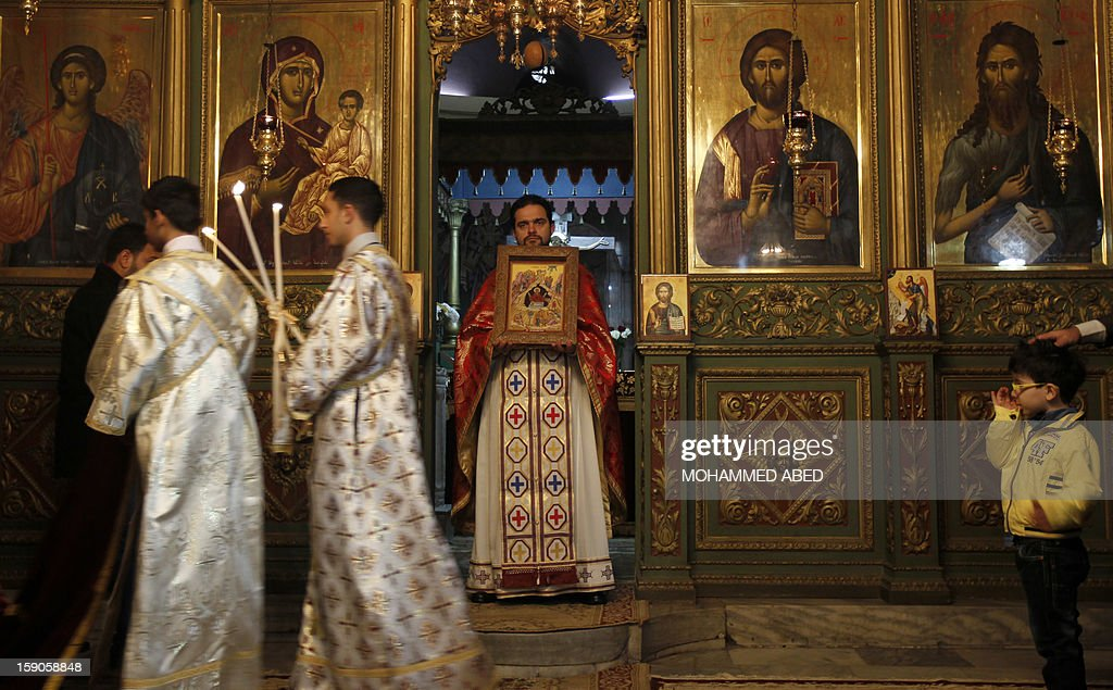 A Palestinian Orthodox Christian priest officiates during a mass at the Church of Saint-Porphyrius during Christmas celebrations on January 7, 2013 in Gaza City. According to the Gregorian calendar, Orthodox Christmas falls 13 days after the December 25 Western feast celebrated in line with the Julian calendar.