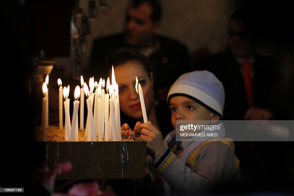 A Palestinian Orthodox Christian young boy his helped to light a candle in a church during Christmas celebrations on January 7, 2013 in Gaza City. According to the Gregorian calendar, Orthodox Christmas falls 13 days after the December 25 Western feast celebrated in line with the Julian calendar.
