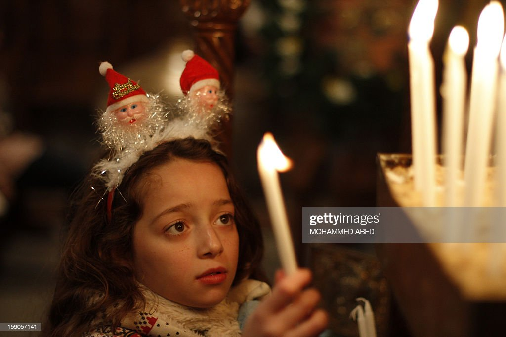 A Palestinian Orthodox Christian young girl lights a candle in a church during Christmas celebrations on January 7, 2013 in Gaza City. According to the Gregorian calendar, Orthodox Christmas falls 13 days after the December 25 Western feast celebrated in line with the Julian calendar.