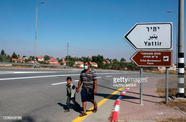 Palestinian Othman Abu Qbeita walks with his son past a road sign indicating the Israeli settlement of Yattir on his way home in Al-Issifer...