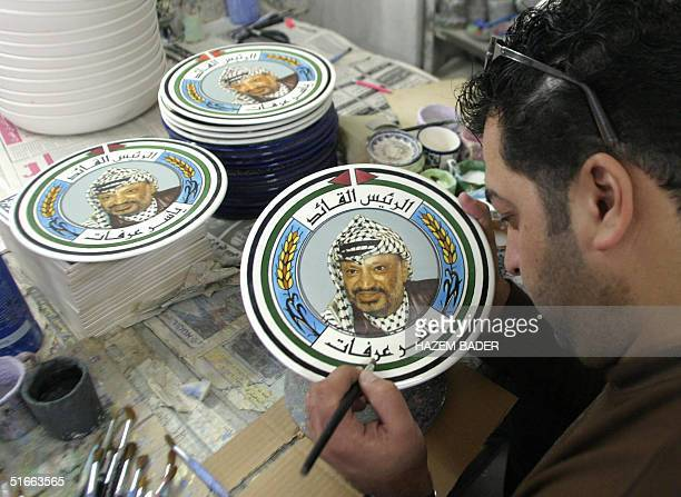 Palestinian painter paints on ceramic plates the portrait of Palestinian leader Yasser Arafat in the West Bank city of Hebron 04 November 2004 Arafat...