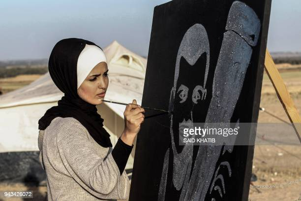 Palestinian painter Reham Al Amawi puts the finishing touch to a poster of Palestinian journalist Yasser Murtaja as fellow journalists take part in a...