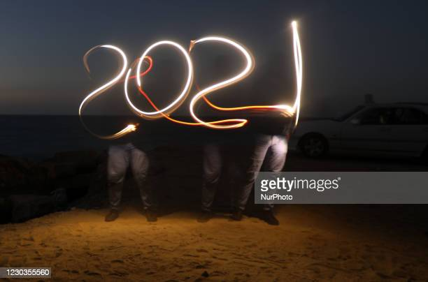 Palestinian paints long exposure 2021 to celebrate the new year in Gaza City, Tuesday, Dec. 29, 2020.