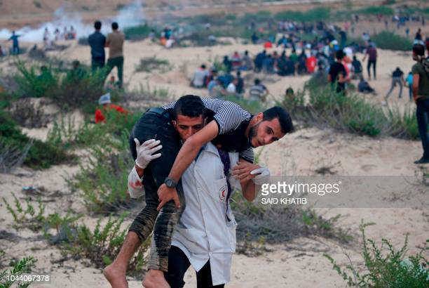 Palestinian paramedic carries an injured protester during a demonstration on the beach near the maritime border with Israel, in the northern Gaza...