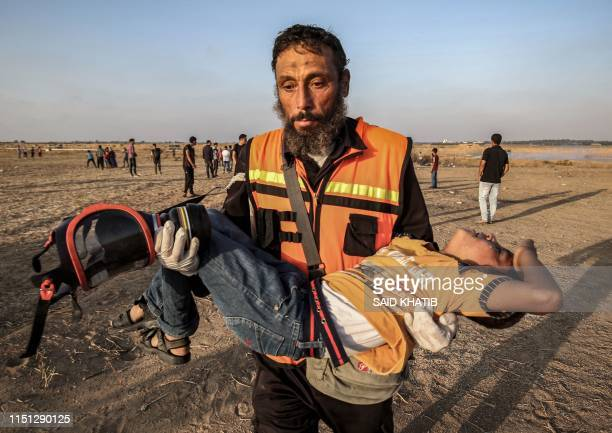 Palestinian paramedic carries away an injured child during a demonstration along the border with Israel east of Khan Yunis in the southern Gaza strip...