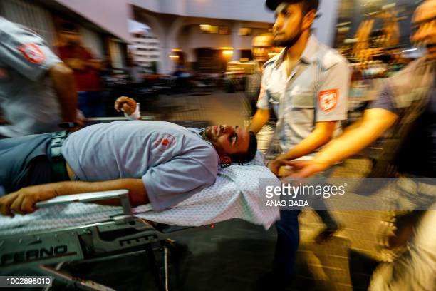 TOPSHOT Palestinian Paramedic wheel an injured man into the alShifa hospital in Gaza City after he was injured by Israeli forces during protests...