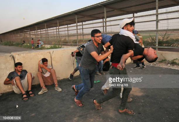 Palestinian paramedics carry an injured protester as people demonstrate at the Erez border crossing with Israel in the northern Gaza Strip on October...