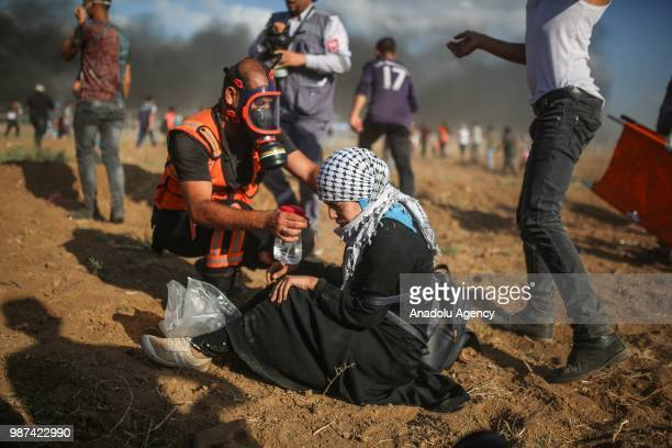 Palestinian paramedics carry an injured protestor as Israeli forces fire tear gas along the border between the Gaza Strip and Israel on the 14th week...