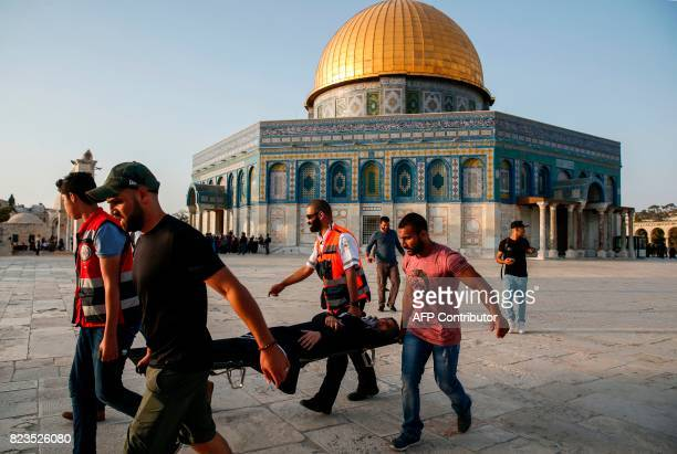 TOPSHOT Palestinian paramedics carry an injured woman on a stretcher past the Dome of the Rock after clashes broke out inside AlAqsa mosque's...