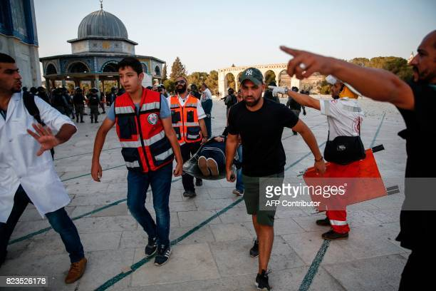Palestinian paramedics carry an injured woman on a stretcher past the Dome of the Rock after clashes broke out inside the AlAqsa mosques compound in...