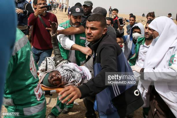 TOPSHOT Palestinian paramedics carry away a woman who was injured during clashes with Israeli forces across the border following a demonstration...