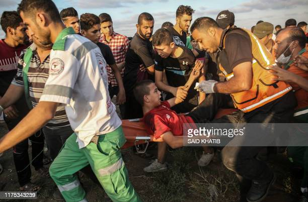 Palestinian paramedics carry away an injured protester during clashes with Israeli forces following a demonstration by the border fence between the...