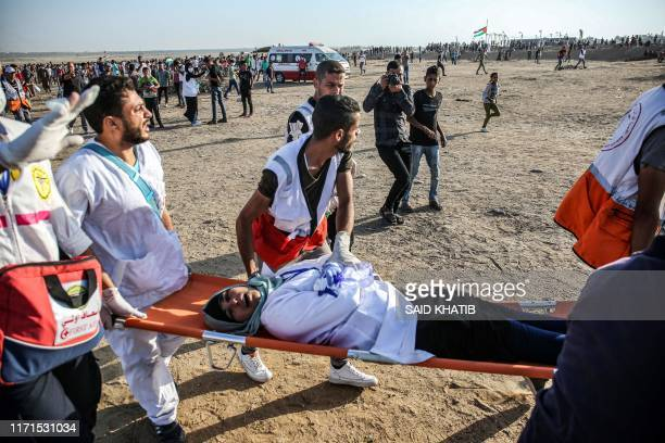 Palestinian paramedics carry away on a stretcher a medic who was injured during clashes with Israeli forces following a demonstration along the...