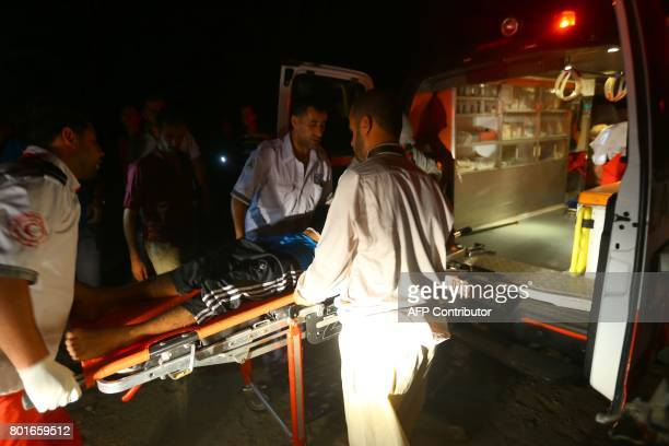 Palestinian paramedics evacuate a wounded man following an Israeli air strike in Gaza City on June 27 2017 Israeli airstrikes hit a series of targets...