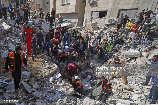 Palestinian paramedics search for survivors under the rubble of a destroyed building in Gaza City on May 16 following massive Israeli bombardment of...