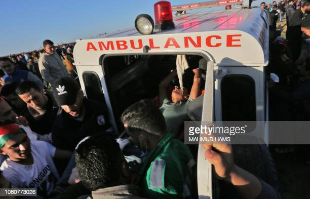 TOPSHOT Palestinian paramedics transport into an ambulance a protester who was injured during clashes with Israeli forces following a demonstration...