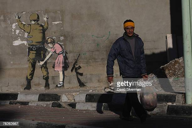 Palestinian passes a wall painting by elusive British graffiti artist Banksy December 5 2007 on a wall in the biblical city of Bethlehem in the West...