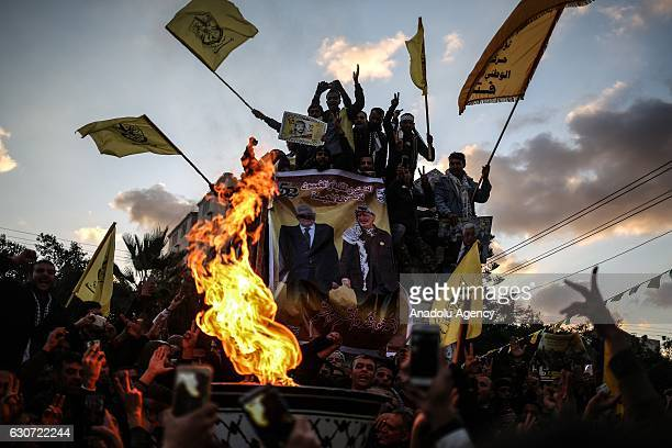 Palestinian people hold placards and flags during the celebrations of the 52nd foundation anniversary of the Fatah movement at Unknown Soldier Square...