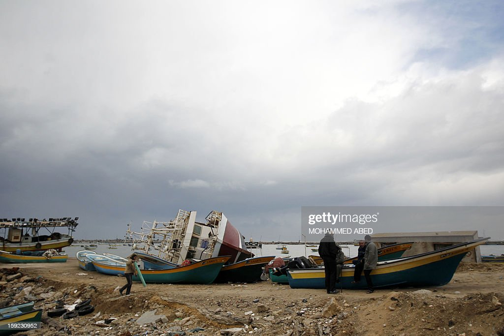 Palestinian people talk near damaged boats after a storm on January 10, 2013 in Gaza City. In Gaza, cold weather and heavy rain flooded several of the tunnels running between the territory and Egypt as in the West Bank city of Ramallah, children and adults, including some policeman stopped their cruiser for an impromptu snowball fight.