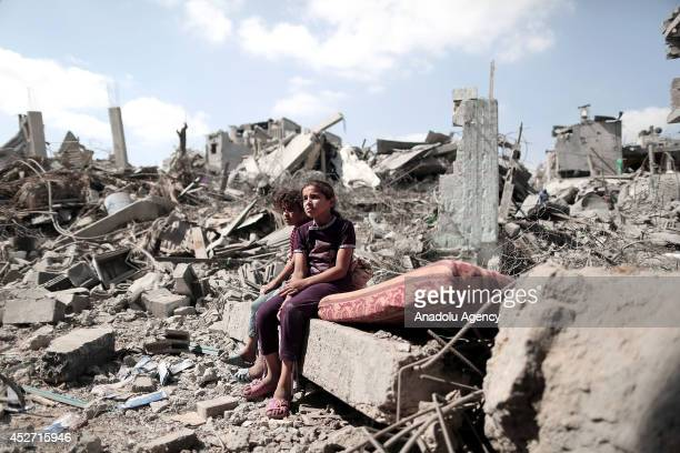Palestinian people walk around and inside the debris of the buildings, destroyed by Israeli fierce bombardments killed around 74 Palestinians and...