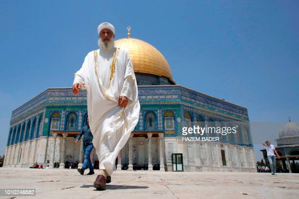 Palestinian people walk in front of the Dome of the Rock at the alAqsa mosque compound in the Jerusalem's Old City during the friday prayer on August...