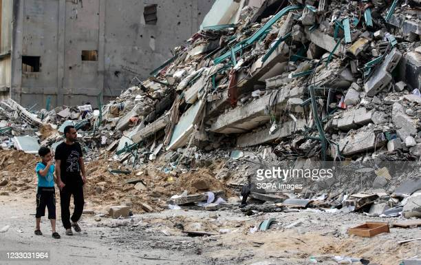 Palestinian people walk past a destroyed tower. A ceasefire between Israel and Hamas, the Islamist movement which controls the Gaza strip, appeared...