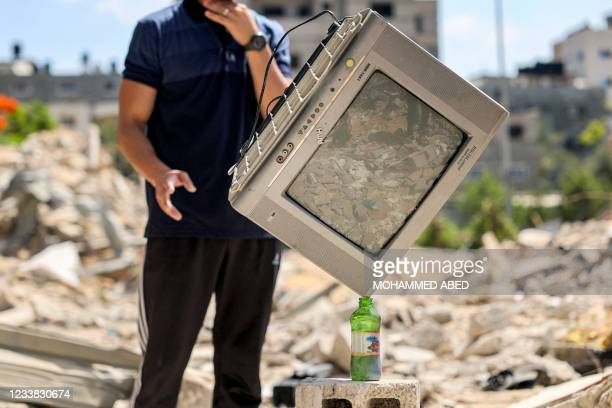 Palestinian performance artist Mohammed al-Shenbari stacks up a television atop a bottle standing on a piece of rubble as he demonstrates his skills...