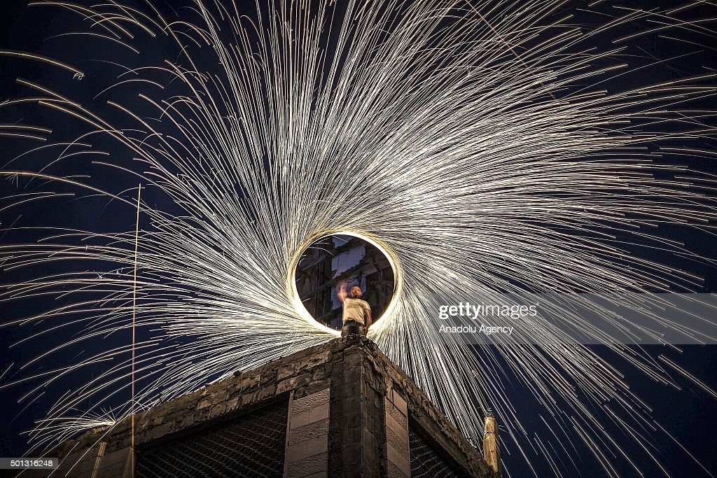 A Palestinian performs to amuse people with a wire which ignites sparks during holy month of Ramadan, on the top of a debris in front of Italian Tower, on June 22, 2015, in Gaza City, Gaza.