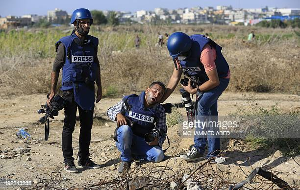 A Palestinian photographer reacts after he was wounded during clashes between Palestinian protestors and Israeli security forces near the border...