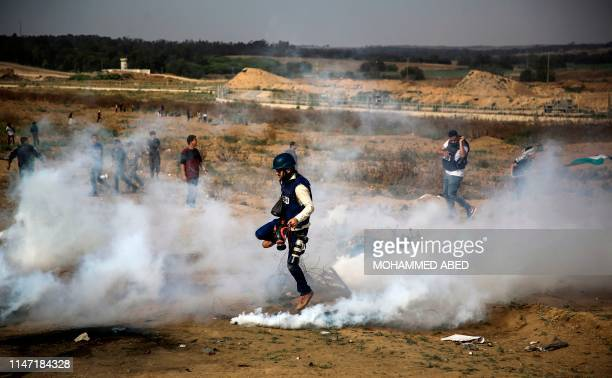 Palestinian photojournalist runs through tear gas fumes amidst clashes between protesters and Israeli forces during a protest marking al-Quds...