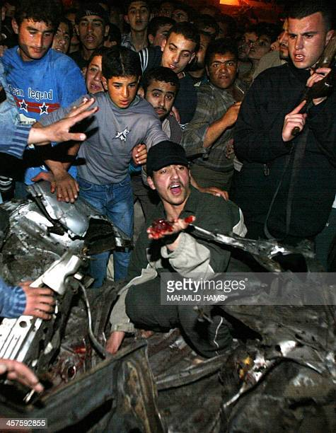 A Palestinian picks up human remains as people gather around the wreckage of a car after it was hit by three missiles shot from an Israeli Apache...