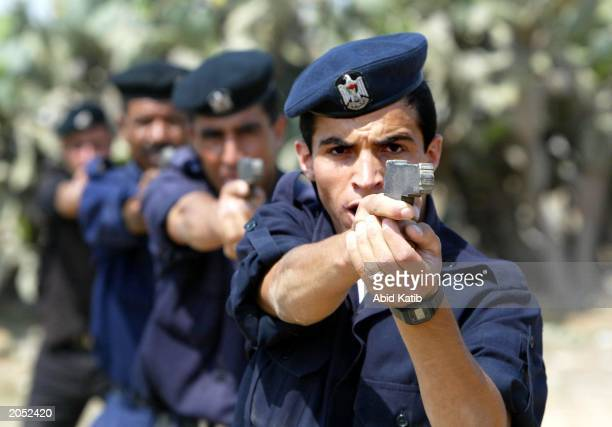 Palestinian police cadets aim their mock guns during training at a compound in Rafah Refugee Camp June 3, 2003 in the Gaza Strip.