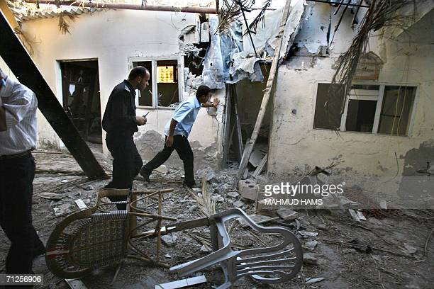 Palestinian police inspect a damaged home hit during an Israeli missile strike in Khan Yunis in the southern Gaza Strip 21June 2006 the second air...