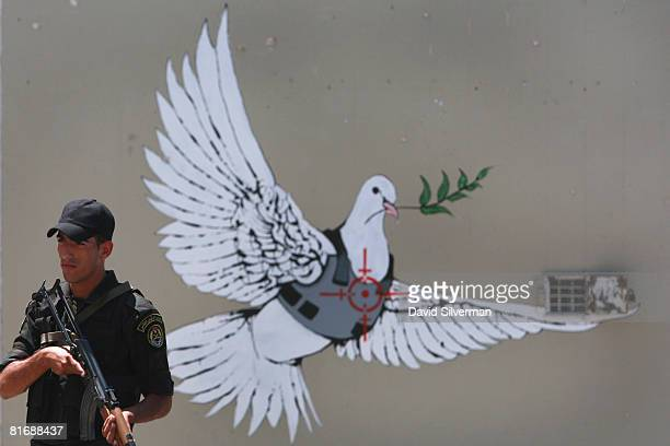 Palestinian police officer stands guard in front of a mural by the British grafitti artist Banksy as he secures the arrival of French President...