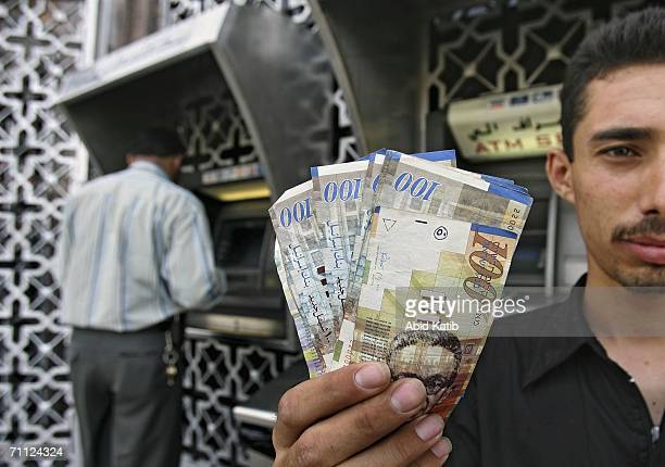 Palestinian policeman displays money, while another one withdraws money from a bank machine, at the Palestine Bank June 5, 2006 in Gaza City, Gaza...