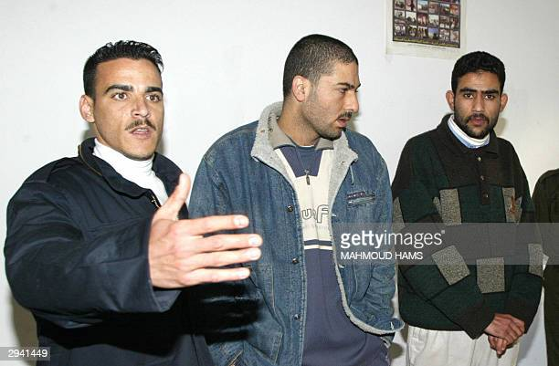 Palestinian policeman gestures as he guards Ahmad Abdel Fattah alSafi and Mohammad alDsouki Kamel Hamad two of four Palestinian suspects brought...