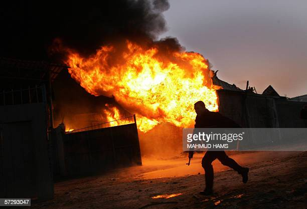 Palestinian Policeman inspects fire from a maitres factory in the Gaza Strip town of Beit Hanun 09 April 2006 following Israeli tanks firing Israel...