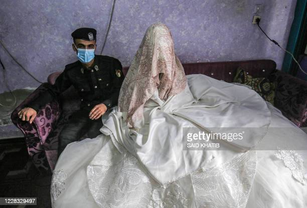 Palestinian policeman Jihad Ahmed poses for a picture with his bride Alaa while both mask and glove-clad due to the COVID-19 coronavirus pandemic...
