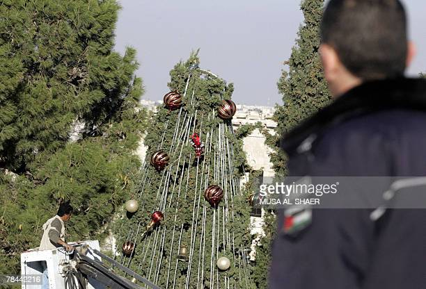 Palestinian policeman keeps watch as a municipal worker decorates the central Christmas tree set up in Manger Square outside the Church of the...