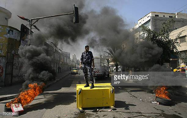 Palestinian policeman stands on a dumpster as he and others close a main road during a protest by Palestinian policemen held to demand salaries from...